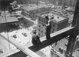 In this photograph contruction workers balance precariously on the exposed girder of a skyscraper under construction. Note the complete lack of safety equipment or harnesses.